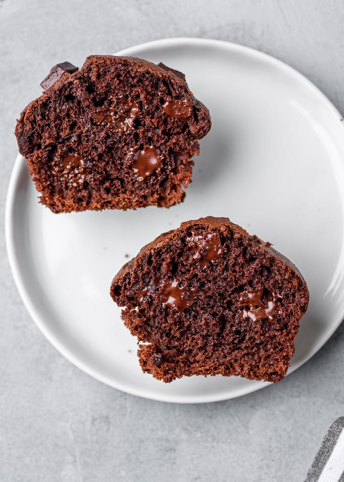 Rozkrojený čokoládový muffin na bílém talíři